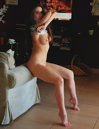 Elina strips on the couch baring her sexy hips and trimmed pussy.