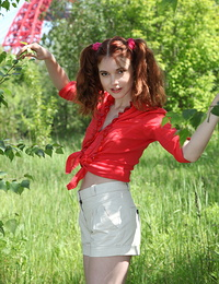 Remarkable redhead teen charmer stripping and demonstrating pussy outdoor on the nature.